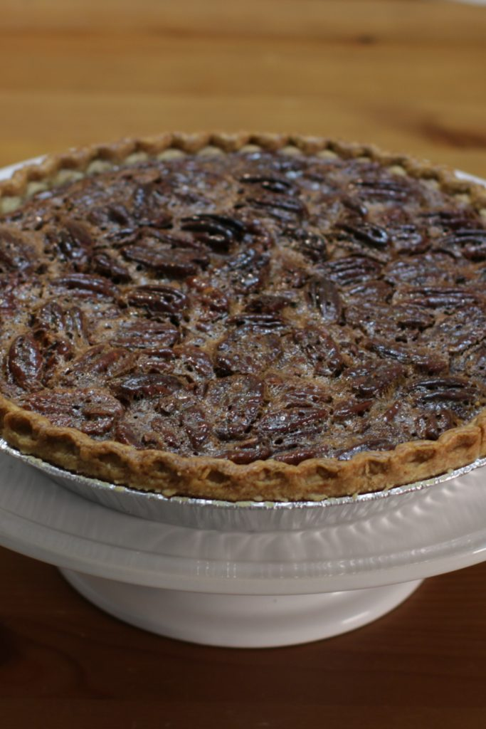 Pecan pie in its aluminum pan on a wooden table.