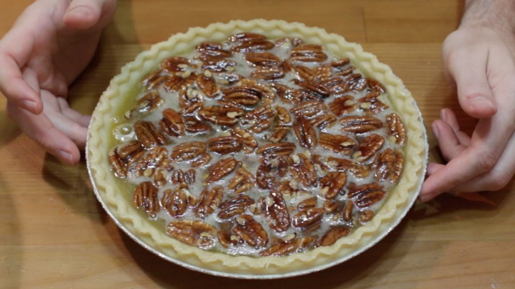 Unbaked pecan pie on a wooden table.