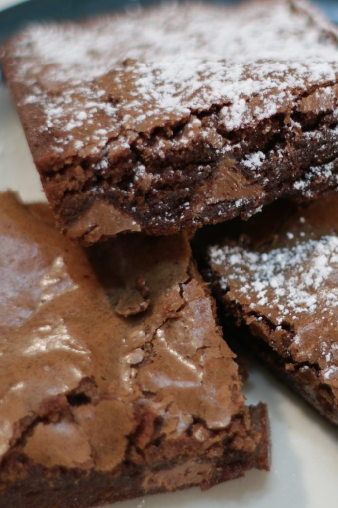 Easy homemade brownies on a plate with powdered sugar on them.