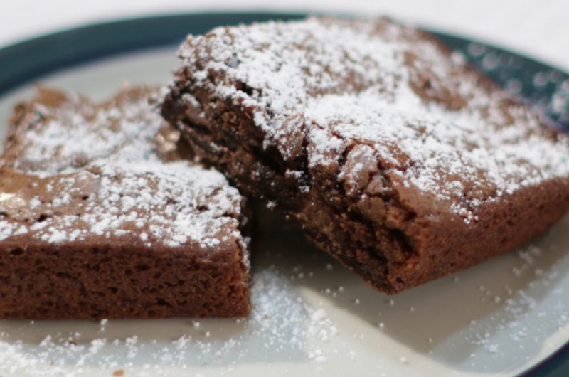 Two homemade brownies with powdered sugar on a plate.