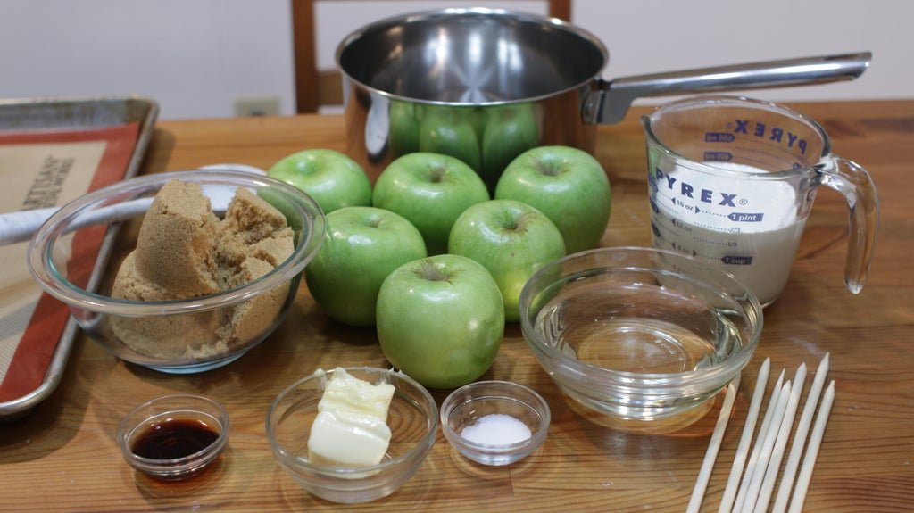 Several ingredients in bowls on top of a wooden table including apples, brown sugar, butter, etc.