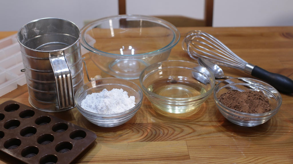 Cocoa powder, coconut oil, and powdered sugar in glass bowls on top of a wooden table.