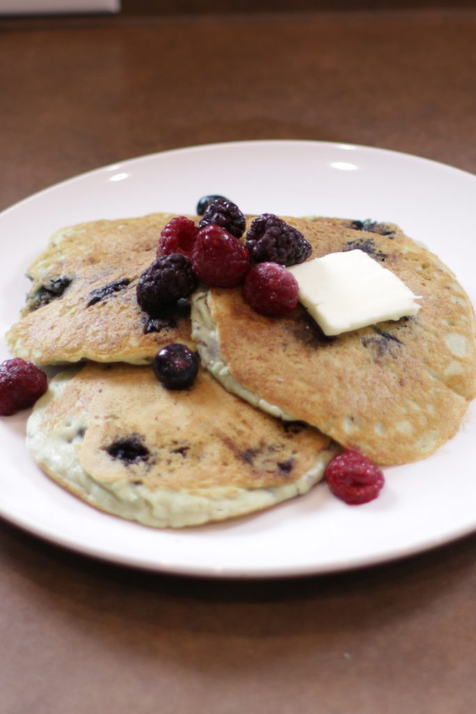 Plate of blueberry keto pancakes with butter and berries.