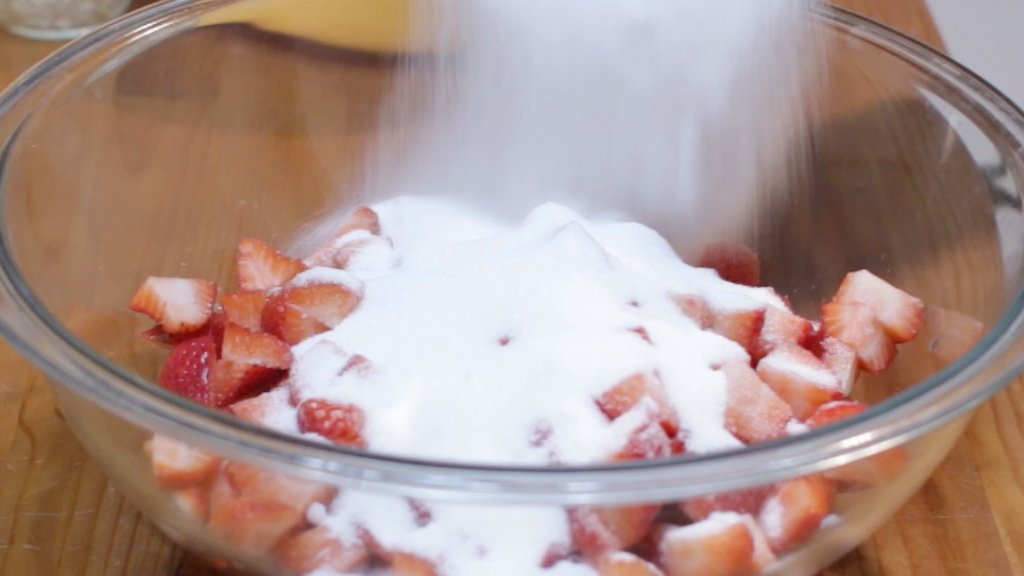 White sugar being added to a bowl of strawberries.