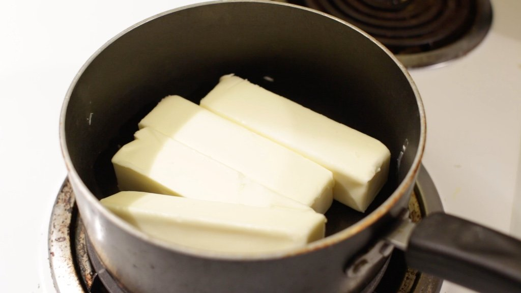 1 pound of unsalted butter in a medium pot on a stovetop burner.