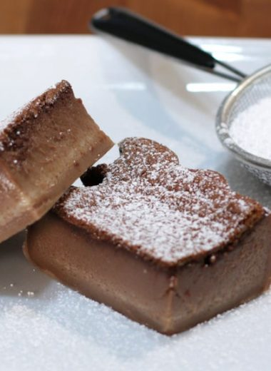 chocolate magic cake slices on a white plate next to powdered sugar