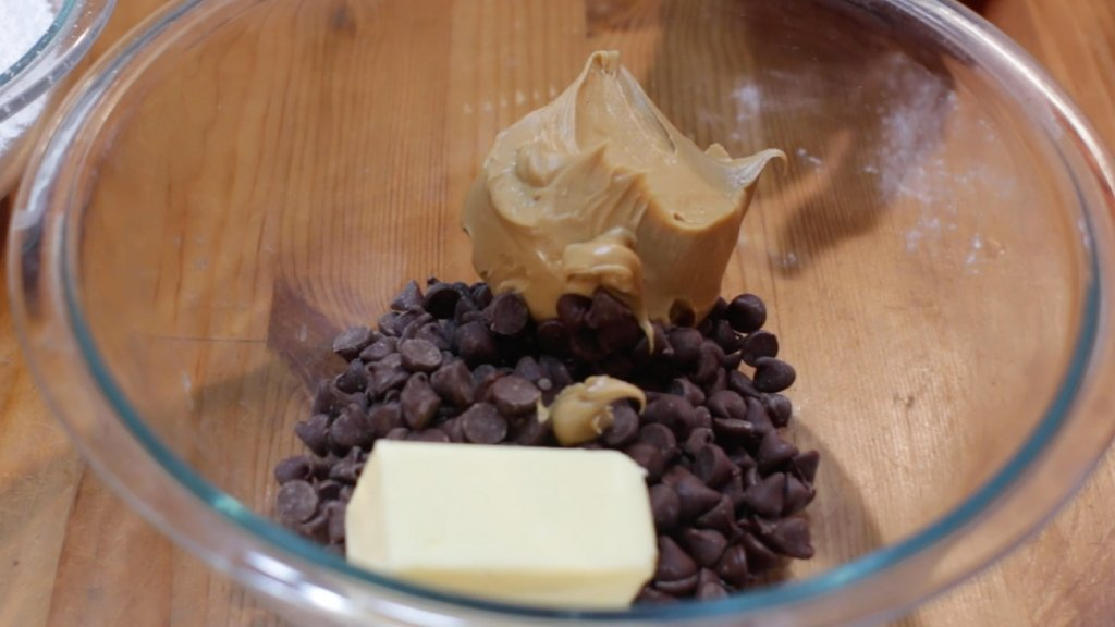 Peanut butter, chocolate, and butter in a medium glass bowl.