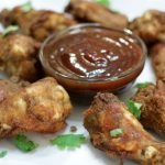 Plate with barbecue sauce and crispy baked oven wings