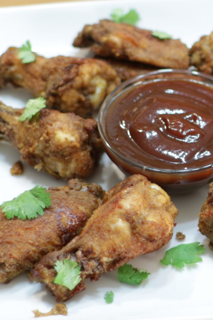 Plate with barbecue sauce and crispy baked chicken wings.