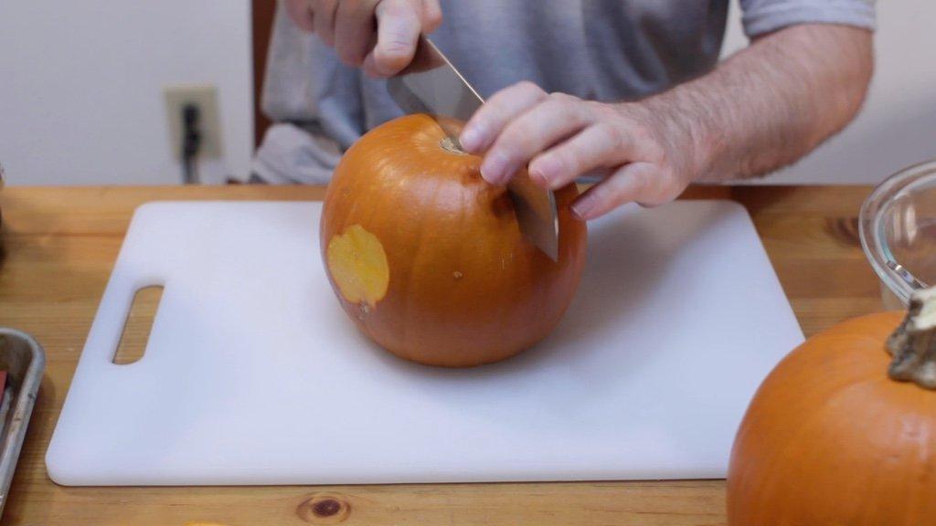 Hand cutting a pumpkin in half.