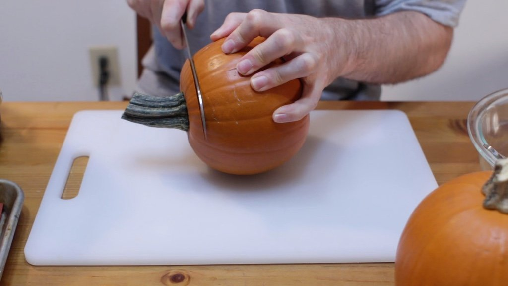Hand cutting a pumpkin on a white cutting board with a knife.