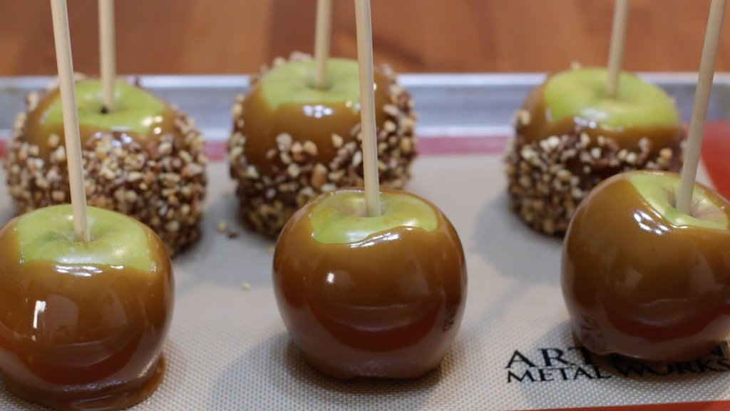 Six dipped caramel apples sitting on sheet pan.