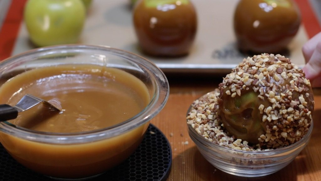 Homemade caramel apple being dipped into a bowl of nuts.