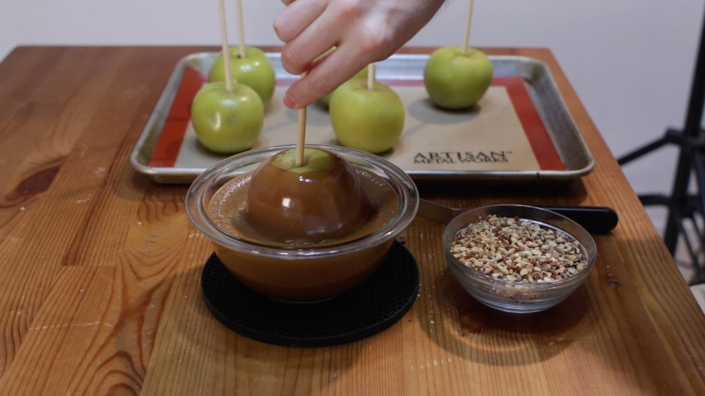 Hand dipping an apple into homemade caramel.