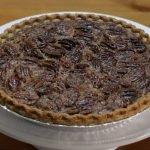 Easy pecan pie on a white cake pedestal