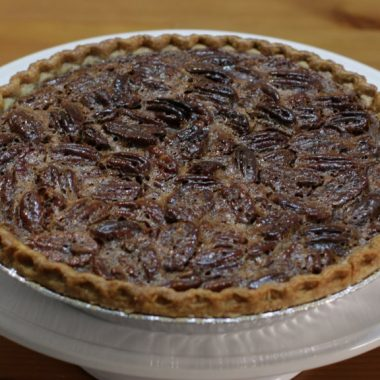 Easy pecan pie on a white cake pedestal