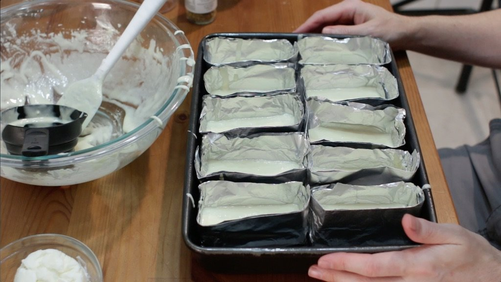 Several aluminum foil Twinkie pans filled with cake batter.