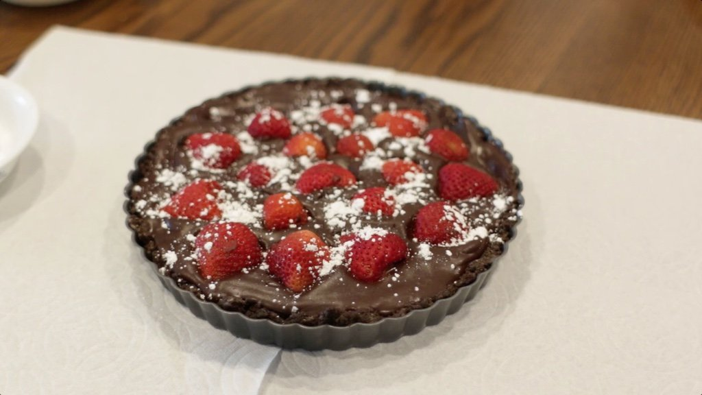 Freshly made gluten dairy free chocolate strawberry tart on a counter.