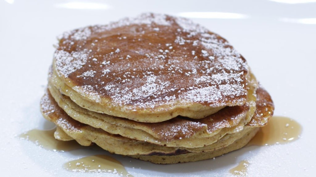 Plate with pumpkin pancakes topped with butter, maple syrup, and powdered sugar.