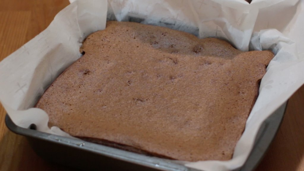 Freshly baked chocolate magic cake in a parchment paper lined baking pan.