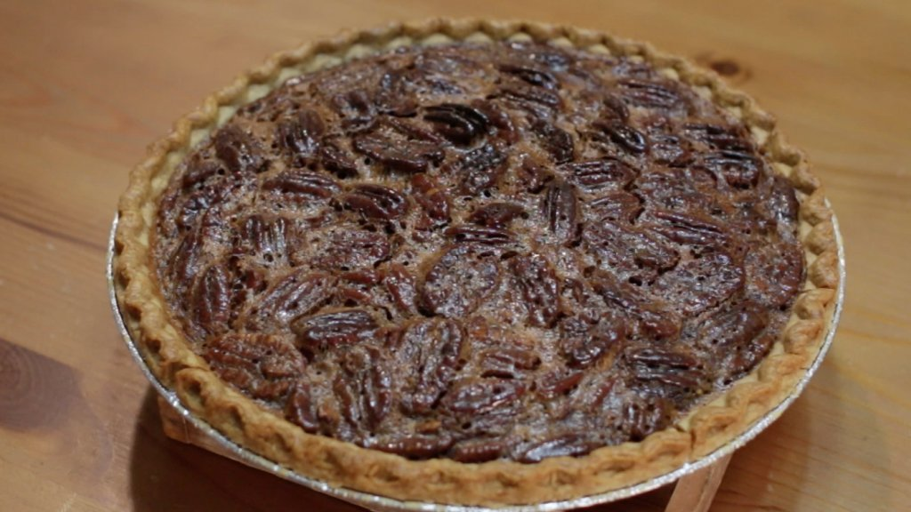 Freshly baked homemade pecan pie on a wooden table.