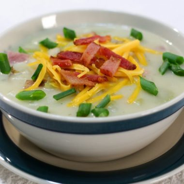 Ham and potato soup topped with bacon and cheese in a bowl.