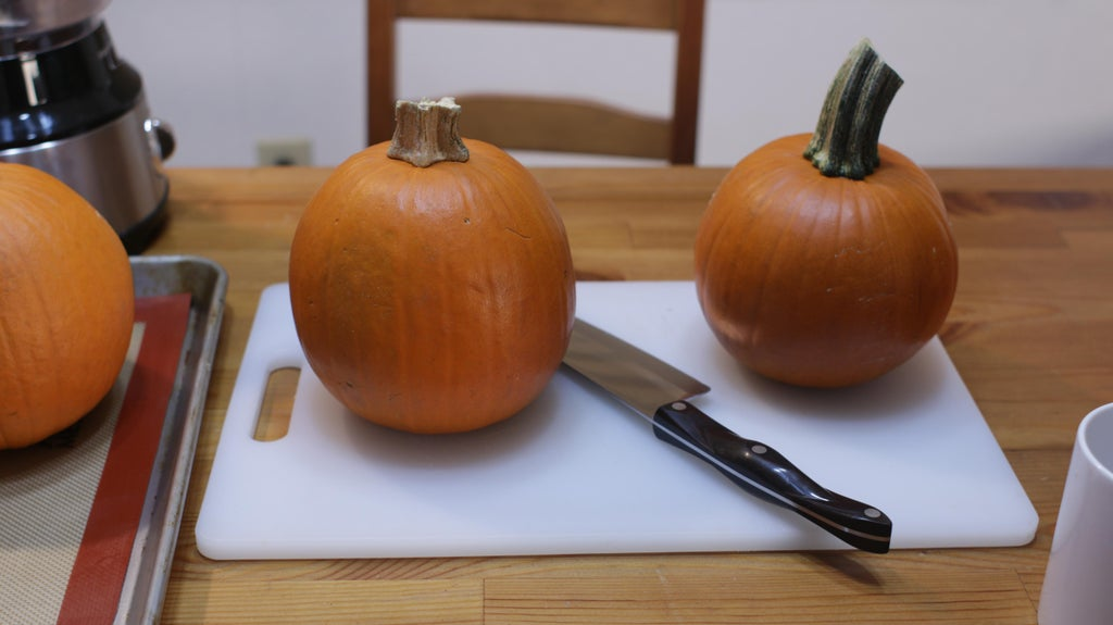 Three small pumpkins on a table with white cutting board, knife, and food processor.