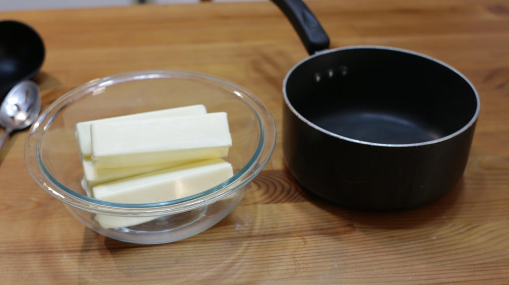 Butter in a bowl next to a pot on a table.