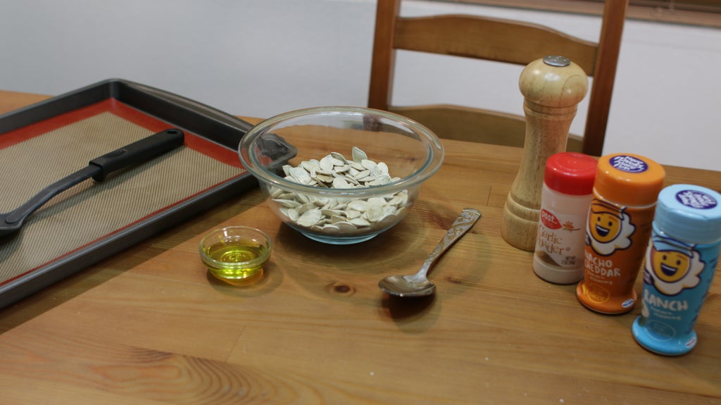 pumpkin seeds and oil in glass bowls on a wooden table.