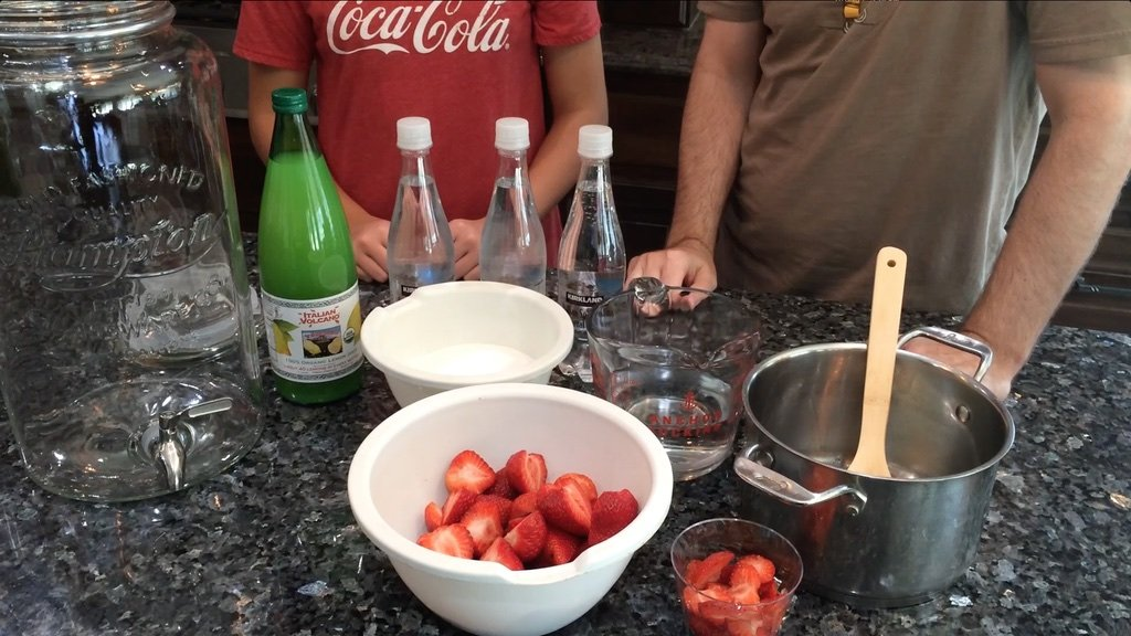 Sparkling water, strawberries, sugar, lemon juice on a counter.
