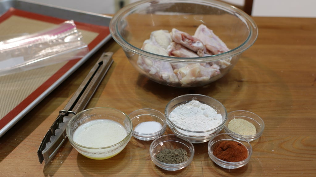 Bowl of uncooked chicken wings, and other ingredients in bowls on a wooden table.