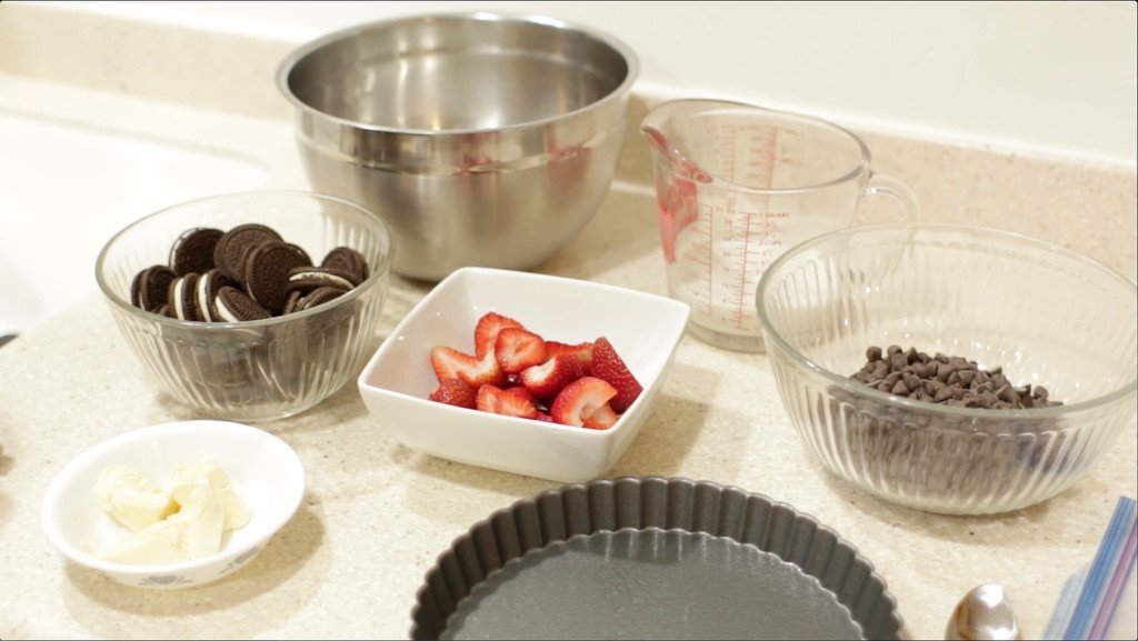 dairy free chocolate chips, strawberries, gluten free oreos, etc. in bowls on a counter.