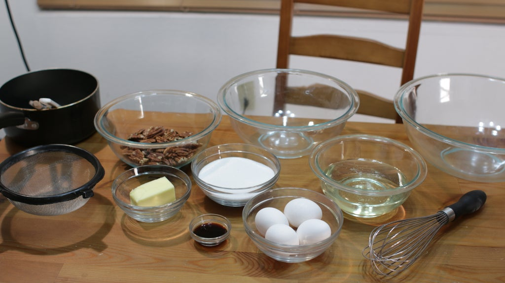 Several ingredients in glass bowls with pecans, butter, sugar, eggs, etc.