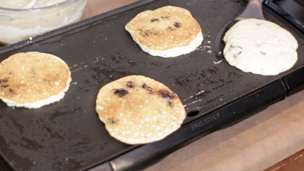 Electric griddle with keto blueberry pancakes on it.