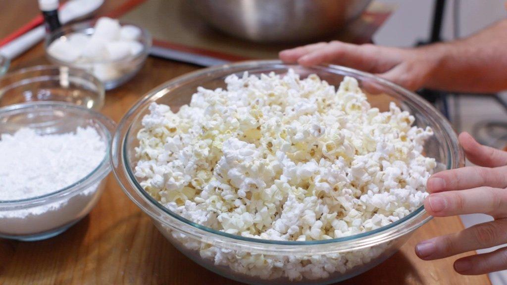 Large glass pyrex bowl full of popped popcorn.