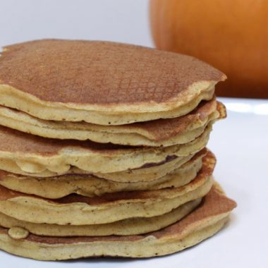 Stack of pumpkin pancakes on a white plate