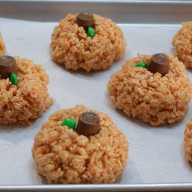 Pumpkin rice krispies treats on a sheet pan with parchment paper.