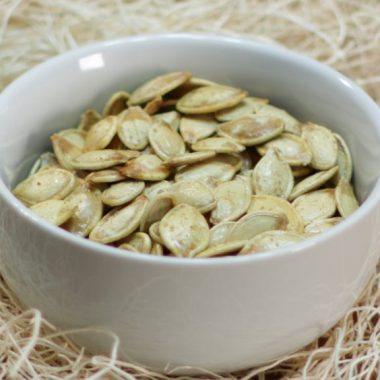 White bowl full of roasted pumpkin seeds