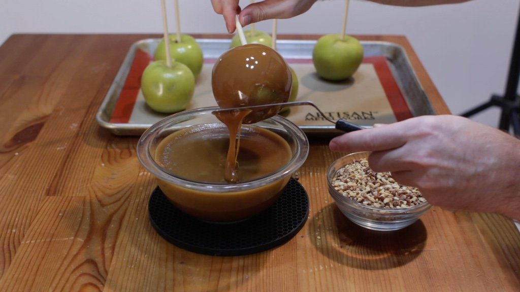 Hand scraping off the homemade caramel from the bottom of a dipped apple.