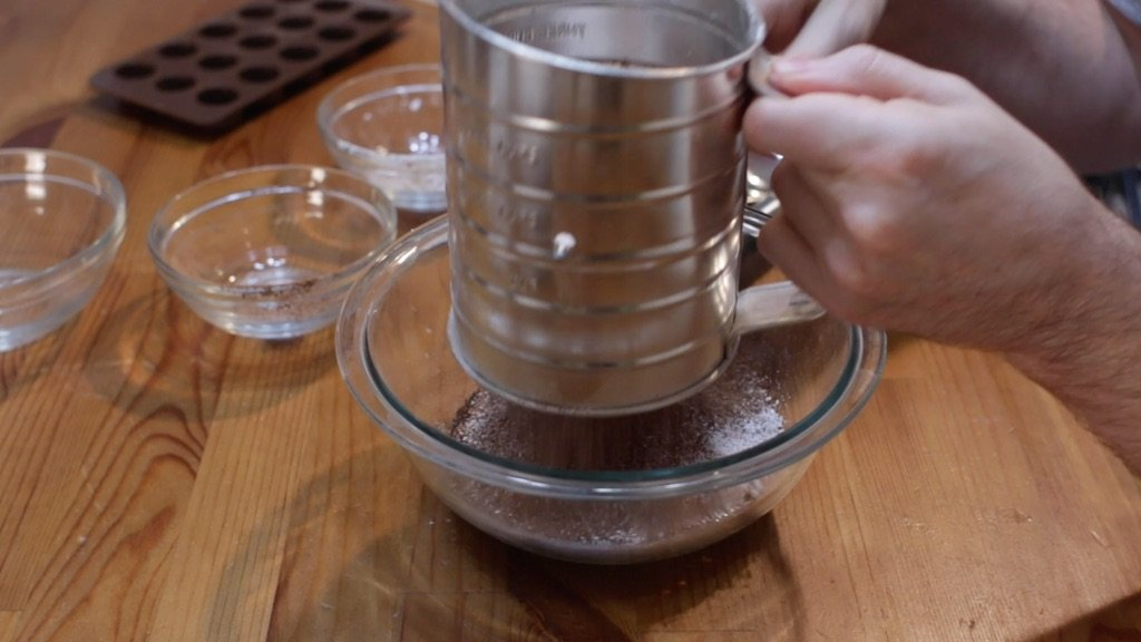 Hand sifting cocoa powder and powdered sugar into a bowl of melted coconut oil.