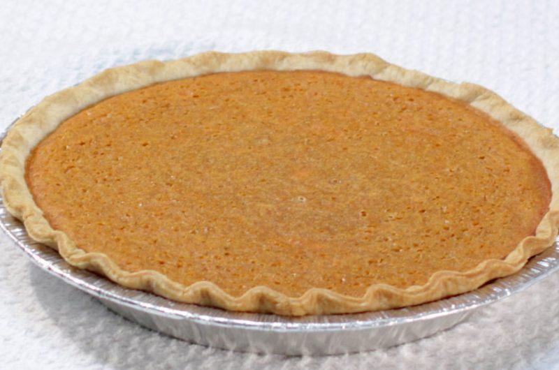 Sweet potato pie on a white table.