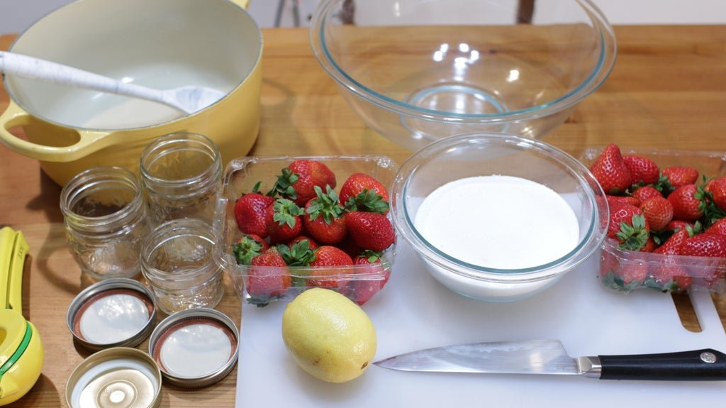 Strawberries, sugar, lemon and bowls on a wooden table.