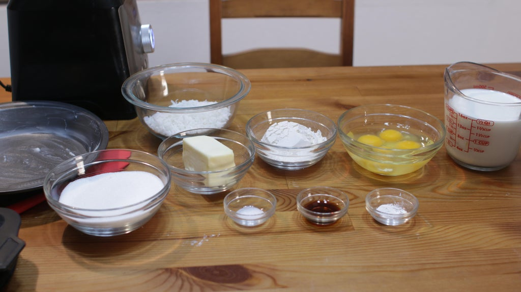 Several ingredients including milk, eggs, flour, butter, coconut, sugar, in glass bowls on a wooden table.