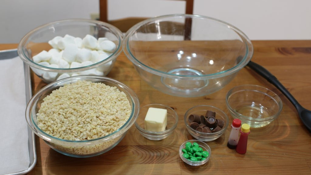 Several ingredients in bowls on a table including marshmallows, rice Krispies, butter, Rolos, green M&Ms, etc.