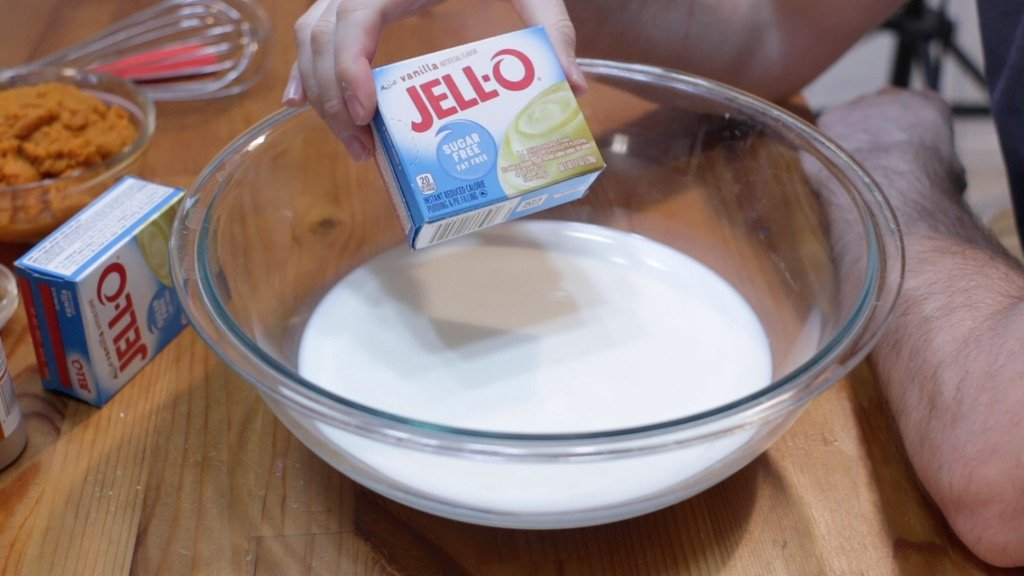 Hand holding a box of Jello instant vanilla pudding over a bowl of milk.