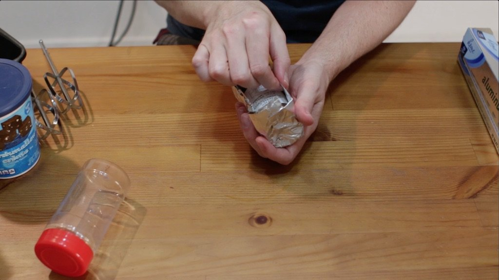 Hand folding aluminum foil around a spice container.