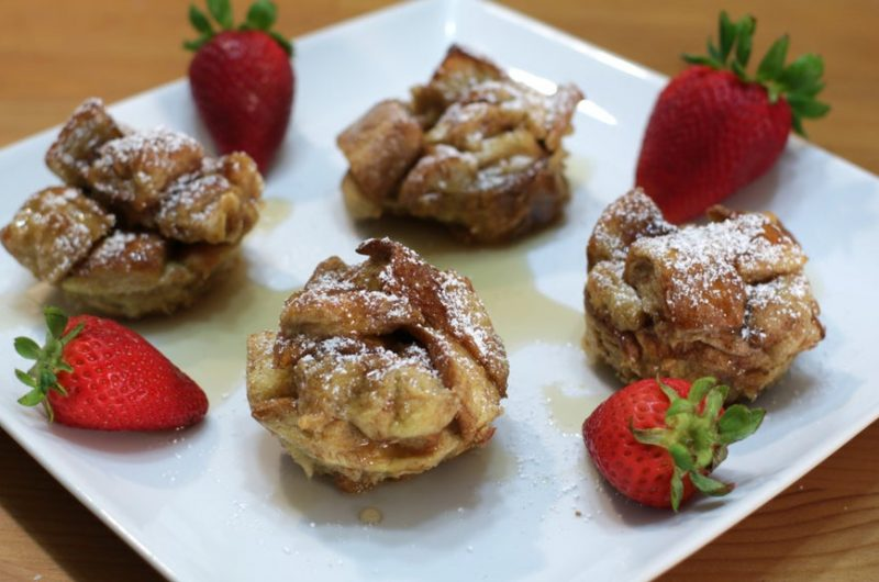 Four French toast bites on a white plate.