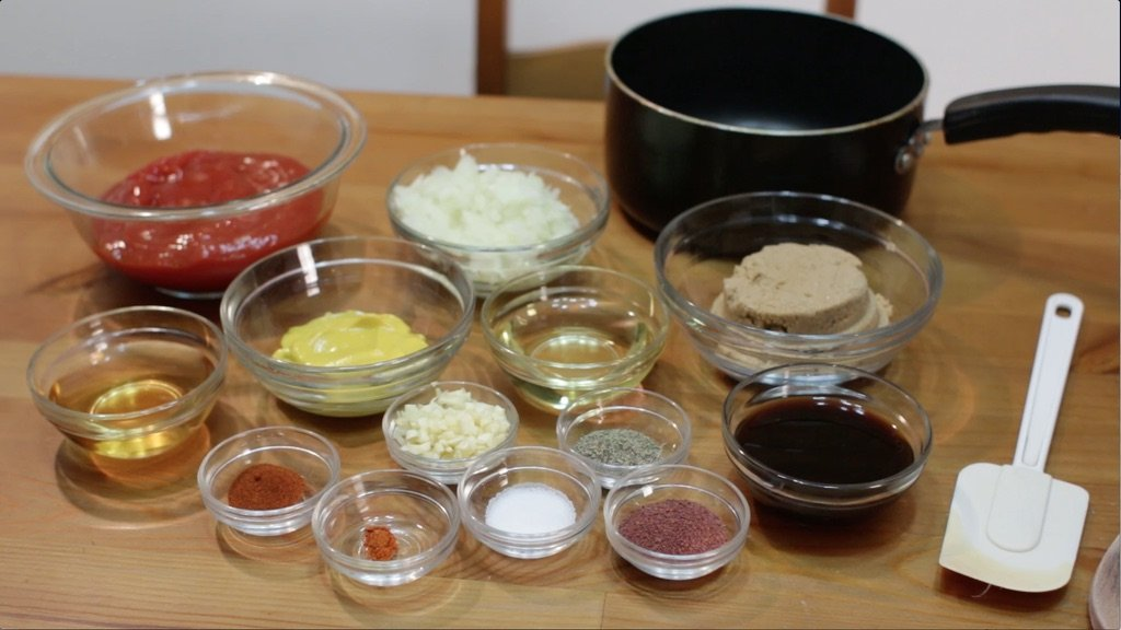 Several different ingredients in glass bowls on top of a wooden table.