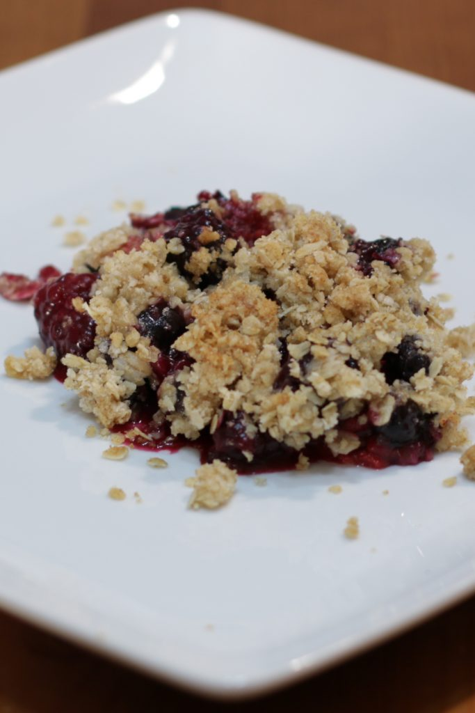 Plate with a scoop of triple berry crisp on it.