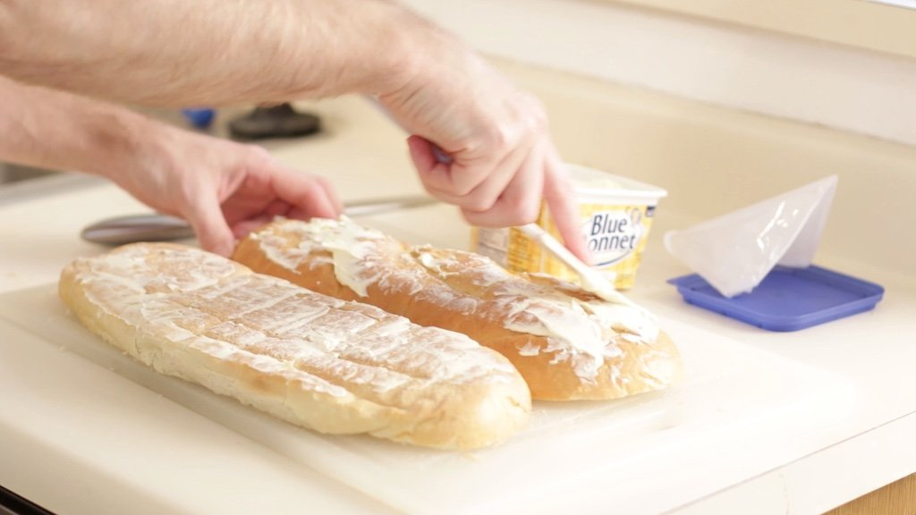 Hand spreading margarine on bread.